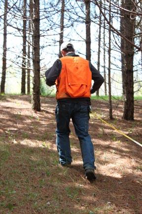 man-using-tap-measure-in-pine-trees